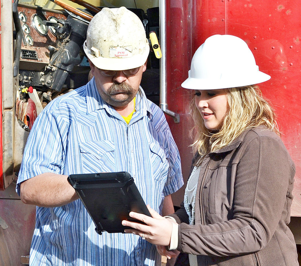 Photo - Abby Sizelove, information technology coordinator for Conquest RT, uses an iPad to demonstrate the app to a driver who will be using it. PHOTOS PROVIDED