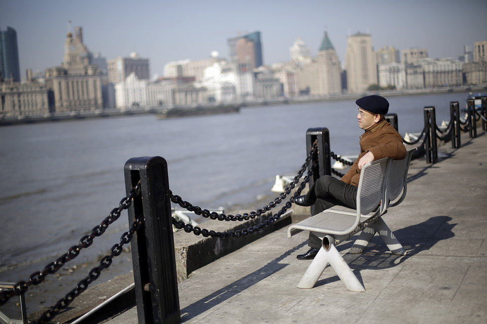 In this Jan. 28, 2013 photo, Chinese-born U.S. scientist Hu Zhicheng sits at the waterfront promenade along the Huangpu River in Shanghai, China. In November 2008, he returned to his native land for what he thought would be a brief visit. Later that month, the day he was supposed to fly back to his family in California, Hu was arrested as a result of of accusations from a business rival. Even though authorities dropped all charges, he still isn't home because of a bizarre set of legal circumstances that prohibit him from leaving China. (AP Photo/Eugene Hoshiko)