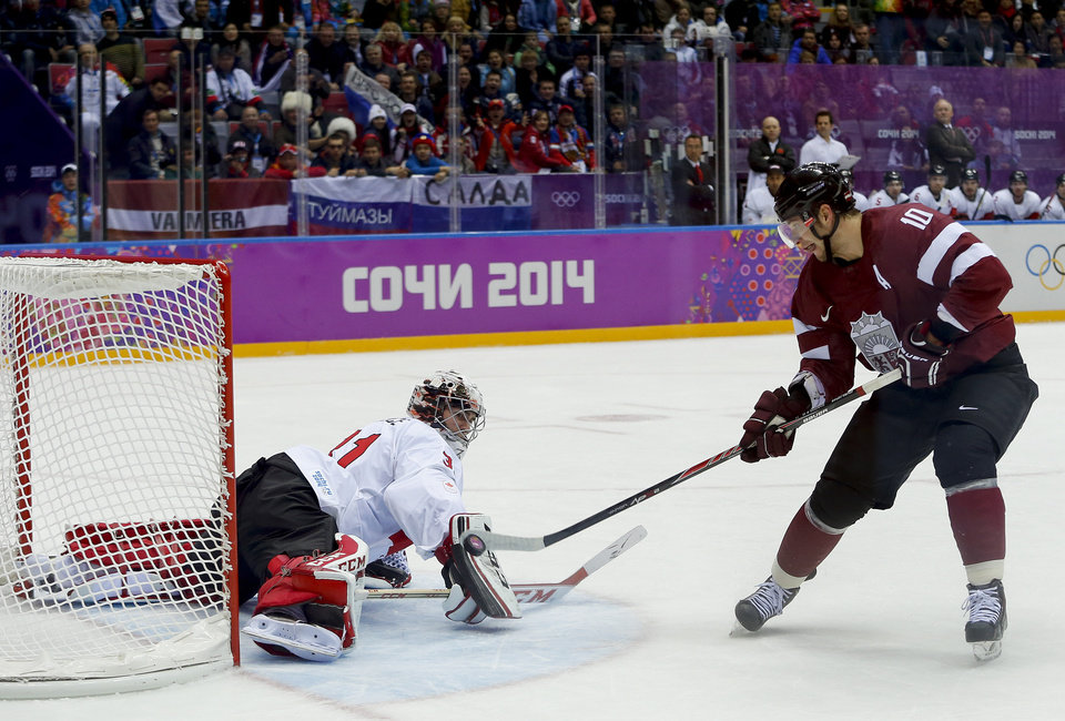 Photo - Latvia forward Lauris Darzins flips the puck past Canada goaltender Carey Price for a goal during the first period of a men's quarterfinal ice hockey game at the 2014 Winter Olympics, Wednesday, Feb. 19, 2014, in Sochi, Russia. (AP Photo/Julio Cortez)