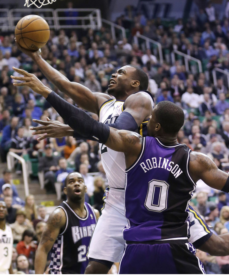 Utah Jazz's Paul Millsap, left, lays the ball as Sacramento Kings' Thomas Robinson (0) defends in the second half during an NBA basketball game Monday, Feb. 4, 2013, in Salt Lake City. The Jazz defeated the Kings 98-91 in overtime. (AP Photo/Rick Bowmer)