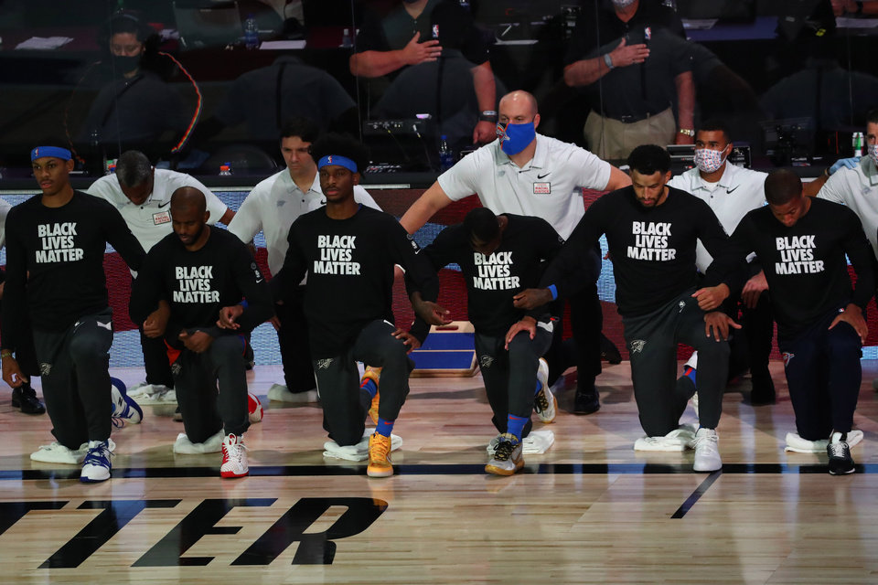 Photo - Aug 18, 2020; Lake Buena Vista, Florida, USA; Oklahoma City Thunder guard Chris Paul (3) kneels during the national anthem before game one of the first round of the 2020 NBA Playoffs against the Houston Rockets at The Field House. Mandatory Credit: Kim Klement-USA TODAY Sports