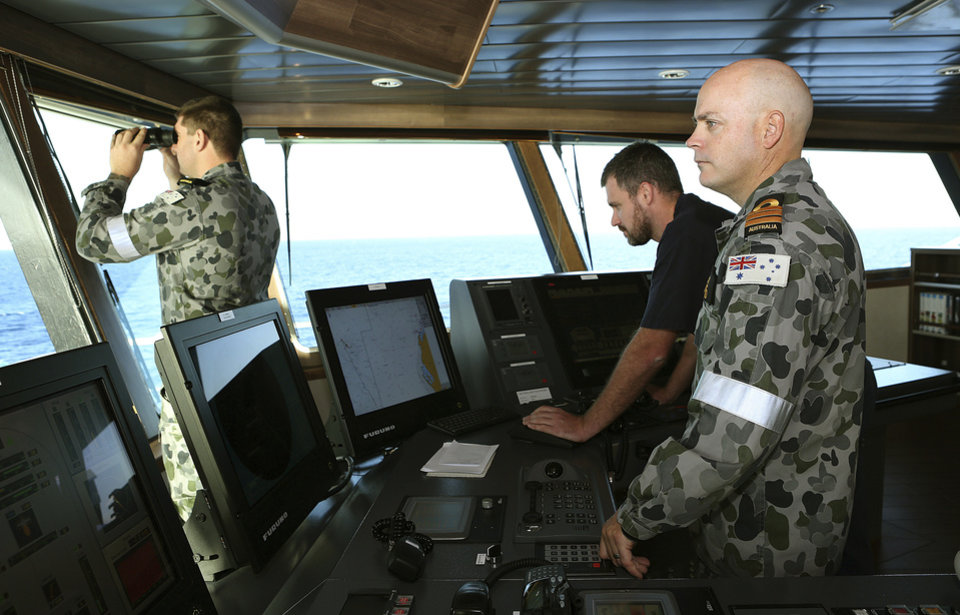 Photo - In this April 5, 2014, photo provided by the Australian Defense Force, Commander James Lybrand, right, watches from the bridge with Captain Nick Woods, Master of the ship, left, as they tow a pinger locator behind the Royal Australian Navy ship Ocean Shield in the southern Indian Ocean. Ocean Shield, which is carrying high-tech sound detectors from the U.S. Navy, is investigating a sound it picked up. (AP Photo/Australian Defense Force, Bradley Darvill) EDITORIAL USE ONLY