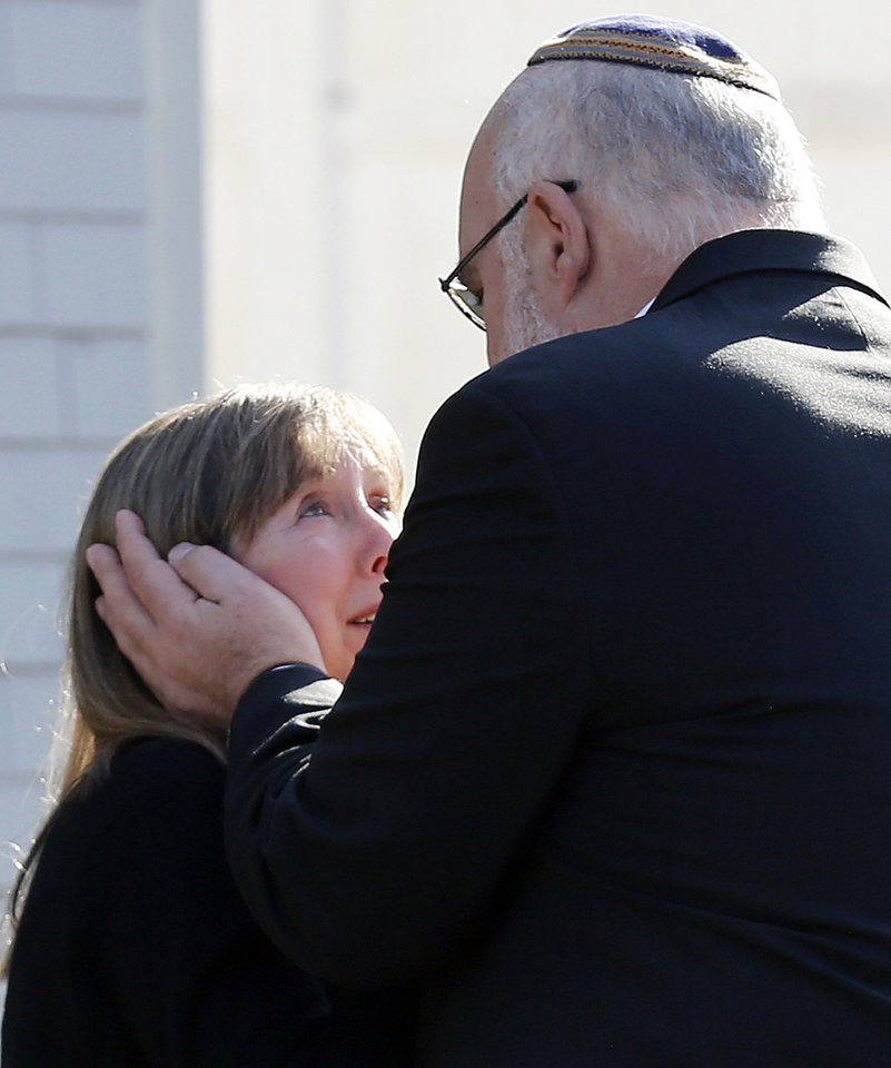 Photo - Two people embrace following a service at the Congregation Adath Israel in Newtown, Conn., Saturday, Dec. 15, 2012. Rabbi Shaul Praver said a six-year-old boy from the congregation was a school shooting victim and that he would be buried on Sunday. (AP Photo/Charles Krupa)