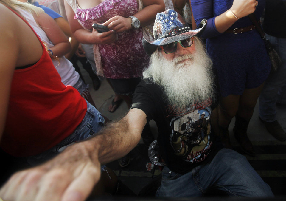 Photo - A fan holds the rail as he dances while country artist Josh Abbott Band performs at OKC Fest in downtown Oklahoma City on Friday, June 27, 2014. OKC Fest is a new two day country music festival with multiple stages downtown. Photos by KT King/The Oklahoman