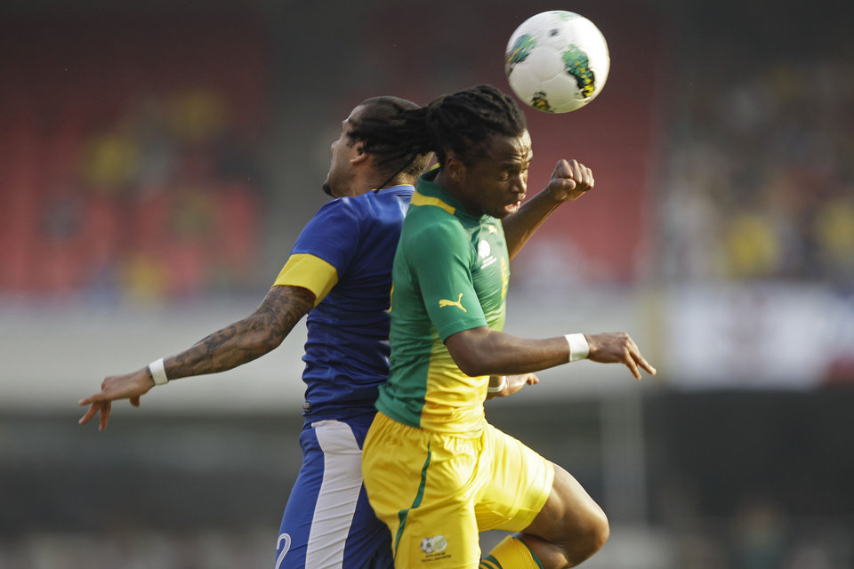 Photo -   Brazil's Daniel Alves, left, heads the ball next to South Africa's Tshabalala during a friendly soccer match in Sao Paulo, Brazil, Friday, Sept. 7, 2012. (AP Photo/Nelson Antoine)
