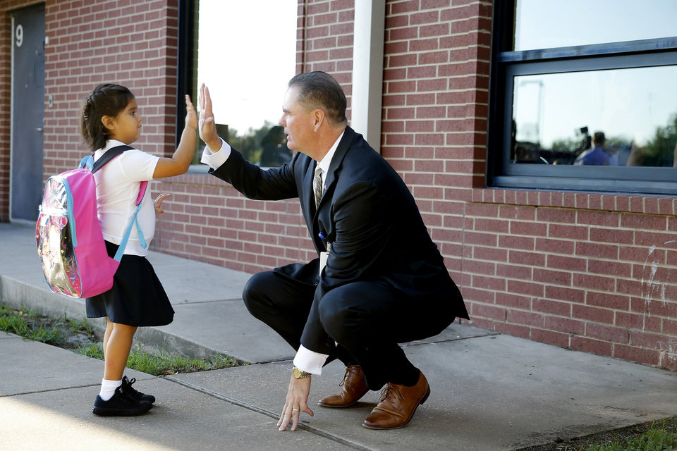 Photo - Oklahoma City Public Schools Superintendent Sean McDaniel greets kindergartner Sophia Ramirez, 5, during the first day of school at Britton Elementary in Oklahoma City, Monday, Aug. 12, 2019. [Bryan Terry/The Oklahoman]