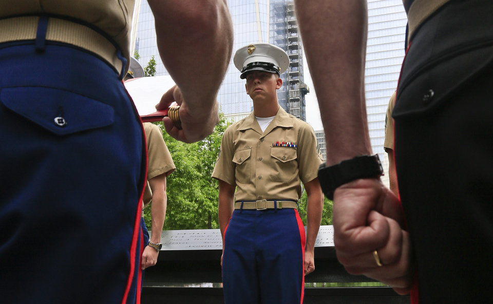 Photo - Marine Lance Cpl. Tyler Atchison, center, listens as his recommendation is read, during a joint U.S. military services re-enlistment and promotion ceremony, Friday May 23, 2014 at the National September 11 Memorial Museum site in New York. Atchison, 22, from Ashland, Ohio and based at Camp Lejeune, N.C., was promoted to the rank of Corporal. (AP Photo/Bebeto Matthews)