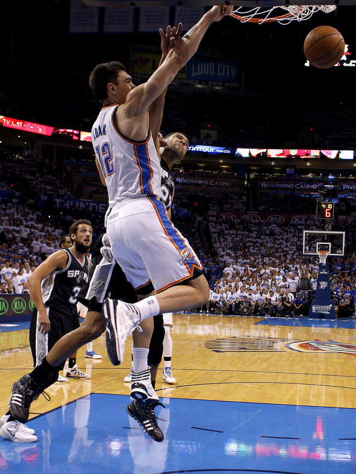 Photo - Oklahoma City's Steven Adams (12) dunks over San Antonio's Tim Duncan (21) during Game 4 of the Western Conference Finals in the NBA playoffs between the Oklahoma City Thunder and the San Antonio Spurs at Chesapeake Energy Arena in Oklahoma City, Tuesday, May 27, 2014. Photo by Bryan Terry, The Oklahoman