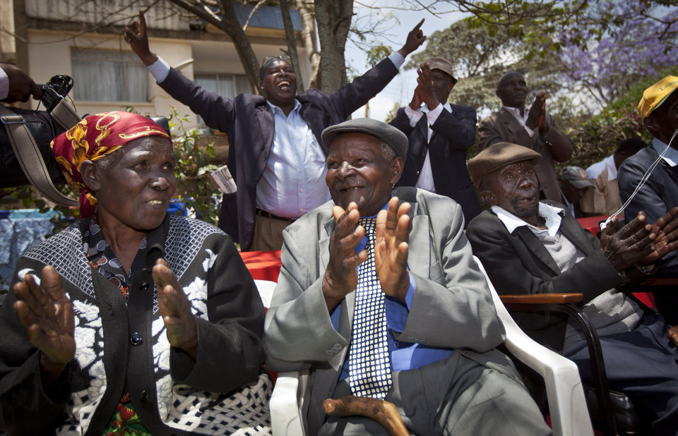 Seated left to right, Kenyans Jane Muthoni Mara, Wambuga Wa Nyingi, and Paulo Muoka Nzili, celebrate the announcement of a legal decision in their case at Britain's High Court concerning Mau Mau veterans, at the offices of the Kenya Human Rights Commission in Nairobi, Kenya Friday, Oct. 5, 2012. Britain's High Court ruled Friday that the three Kenyans tortured during the Mau Mau rebellion against British colonial rule can proceed with compensation claims against the British government. (AP Photo/Ben Curtis)