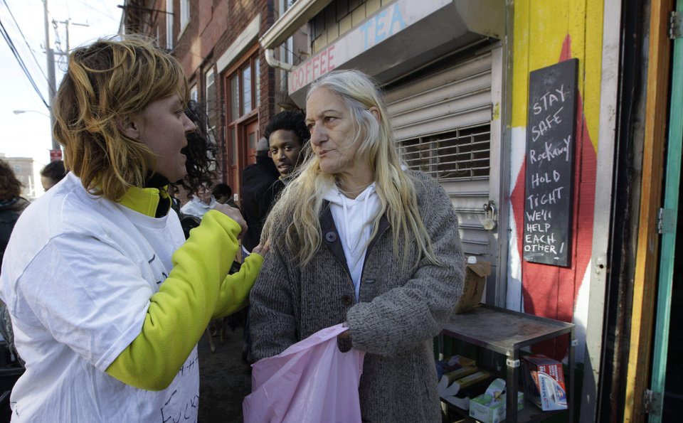 Photo -   Rockaways resident Catherine Yeager, left, talks with fellow resident Linda Allen, who has been living without heat, power, gas, or fresh food all week, after Yeager provided free bagels, a free flashlight and batteries from Yeager, who together with three neighborhood friends set up a donation point outside a small juice bar along a road near the Atlantic Ocean, Saturday, Nov. 3, 2012, in New York. The Rockaways was hard hit by Superstorm Sandy earlier in the week and still has no power. (AP Photo/Kathy Willens)