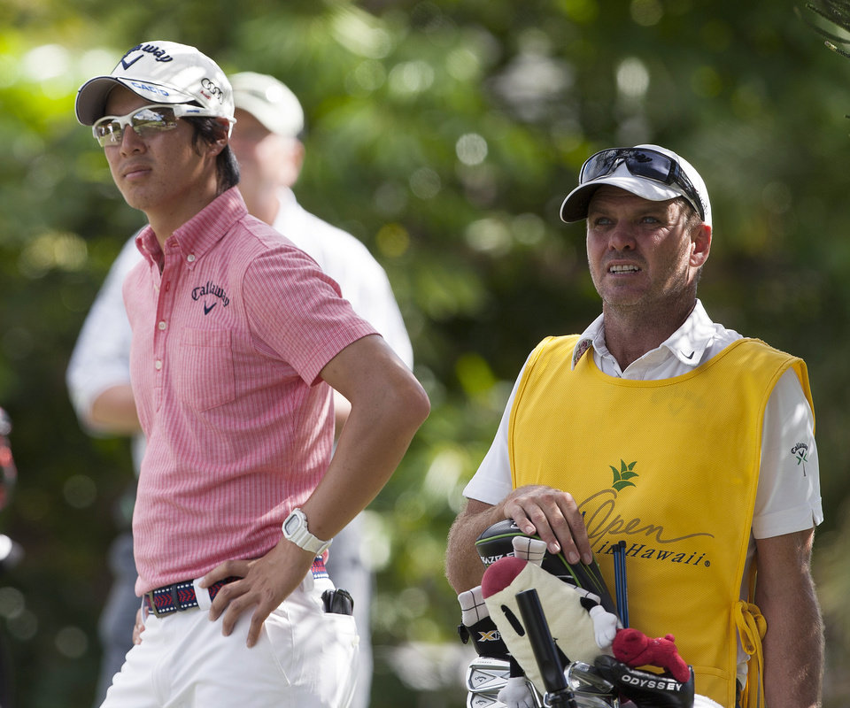 Photo - Ryo Ishikawa, left, of Japan, and his caddie, Simon Clark, stand seen on the fifth tee during the second round of the Sony Open golf tournament, Friday, Jan. 10, 2014, in Honolulu. (AP Photo/Marco Garcia)