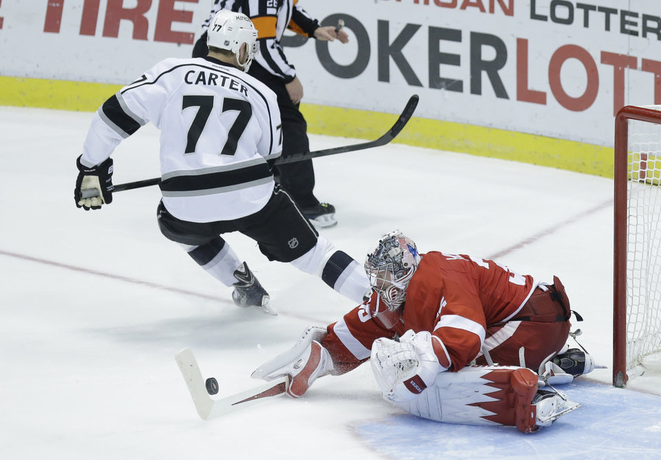 Photo - Detroit Red Wings goalie Jimmy Howard (35) stops a shot by Los Angeles Kings center Jeff Carter (77) during the shootout period of an NHL hockey game in Detroit, Saturday, Jan. 18, 2014. Detroit defeated Los Angeles 3-2. (AP Photo/Carlos Osorio)