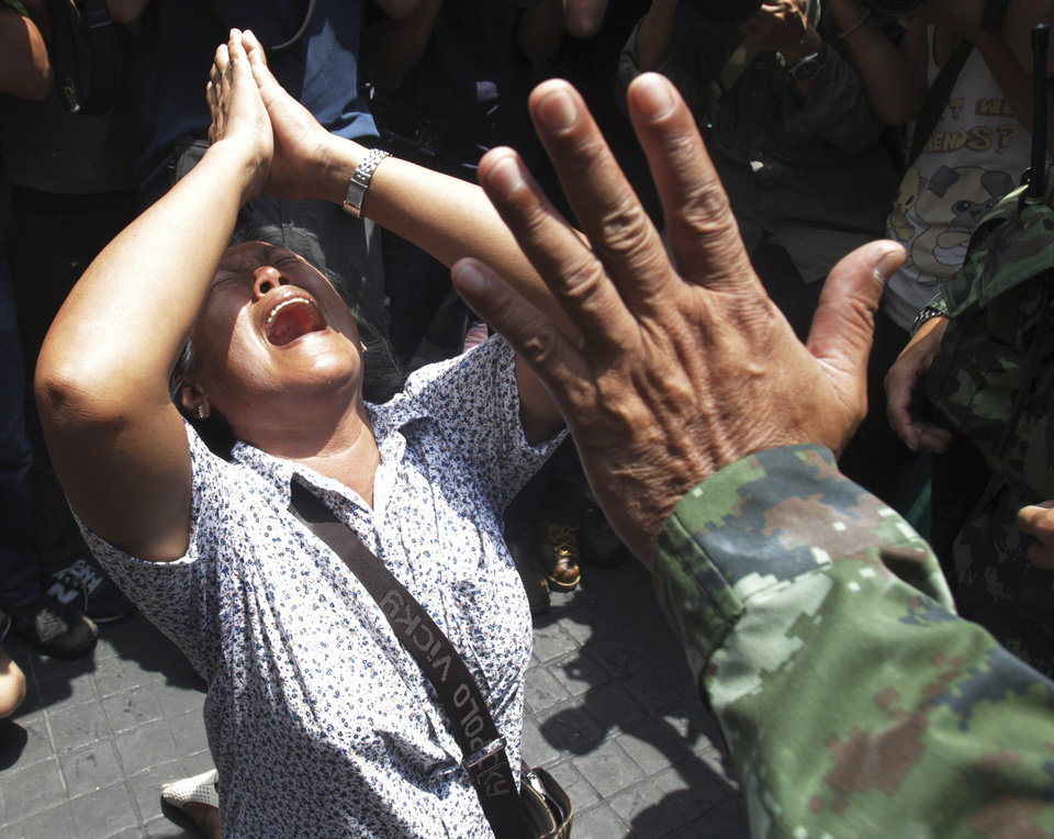 Photo - An anti-coup protester cries as she asks a Thai soldier to go away during a demonstration in Bangkok, Thailand, Sunday, May 25, 2014. The top general in Thailand's ruling junta warned people Sunday not to join anti-coup street protests, saying normal democratic principles cannot be applied at the time, as troops fanned out in central Bangkok to prevent rallies.(AP Photo/Sakchai Lalit)