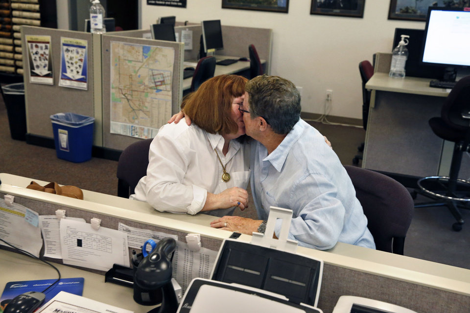Photo - Longtime same-sex couple Jennifer Knight, left, and Felice Cohen kiss after receiving a marriage license, inside the offices of the Boulder County Clerk and Recorder, in Boulder, Colo., Thursday, June 26, 2014. Boulder County Clerk Hillary Hall began issuing licenses a day earlier following a federal appeals court ruling that Utah's same-sex marriage ban is unconstitutional. More couples showed up in Boulder on Thursday to get licenses. (AP Photo/Brennan Linsley)