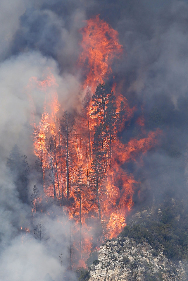 Photo - Flames shoot up over 125-feet high as the Slide Fire burns up Oak Creek Canyon on Friday, May 23, 2014, near Flagstaff, Ariz.  The fire has burned approximately 7,500 acres and is five percent contained. (AP Photo/Ross D. Franklin)