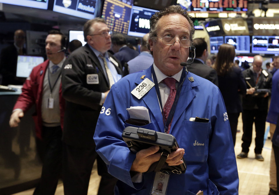 Photo - Trader Steven Kaplan, center, works on the floor of the New York Stock Exchange Tuesday, Feb. 4, 2014. Stocks are mixed on Wall Street after suffering big losses the day before. (AP Photo/Richard Drew)
