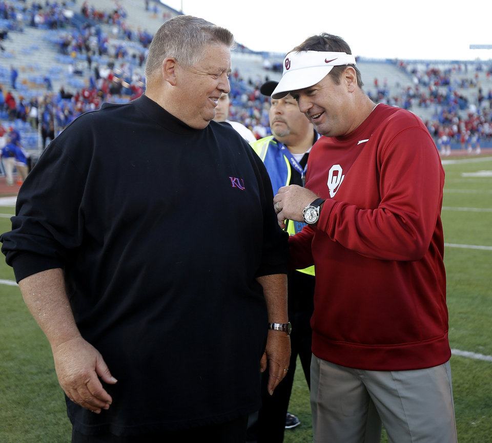 Oklahoma coach Bob Stoops and Kansas coach Charlie Weis talk after a college football game between the University of Oklahoma Sooners (OU) and the University of Kansas Jayhawks (KU) at Memorial Stadium in Lawrence, Kan., Saturday, Oct. 19, 2013. Oklahoma won 34-19. Photo by Bryan Terry, The Oklahoman