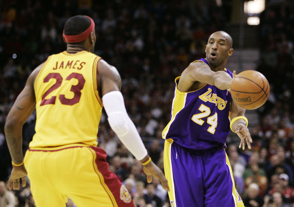 Photo - Los Angeles Lakers' Kobe Bryant (24) fires a pass around Cleveland Cavaliers' LeBron James (23) during the third quarter of an NBA basketball game Sunday, Feb. 8, 2009, in Cleveland. The Lakers beat the Cavaliers 101-91. (AP Photo/Mark Duncan) ORG XMIT: OHMD112