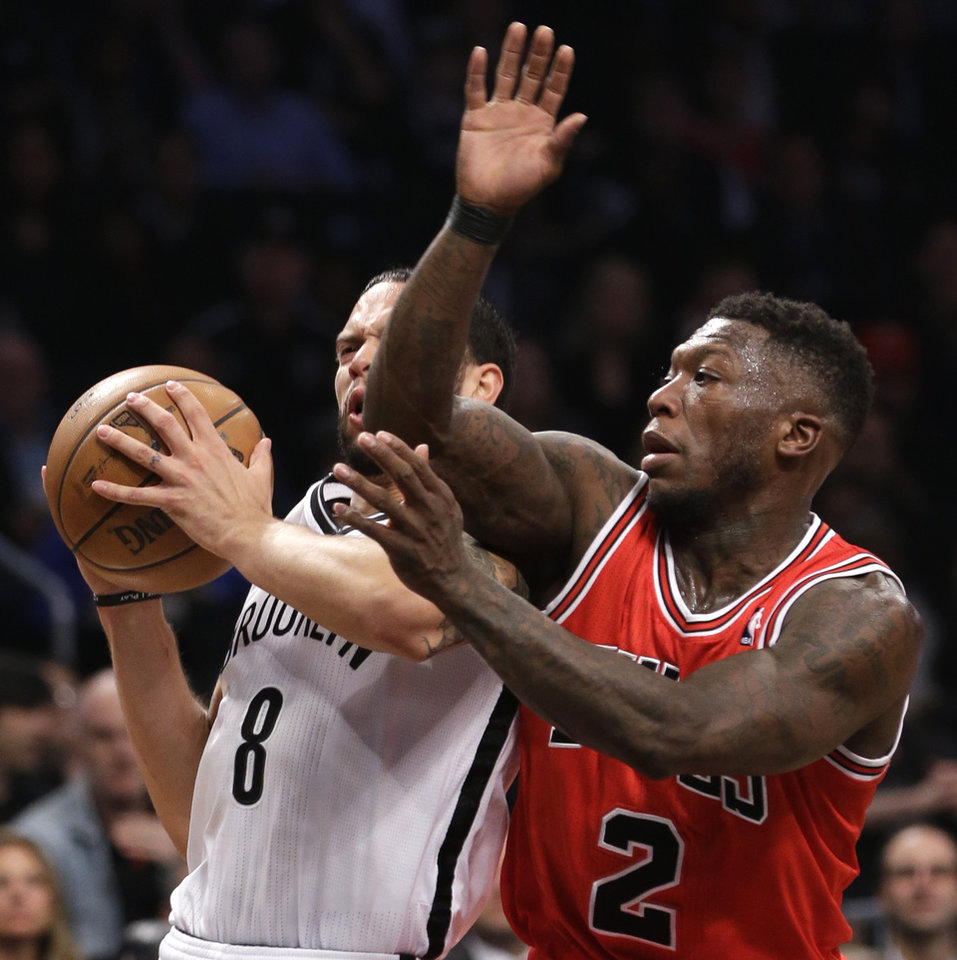 Photo - Brooklyn Nets guard Deron Williams (8) collides with Chicago Bulls guard Nate Robinson (2) as he drives toward the basket in the first half of Game 5 of their first-round NBA basketball playoff series, Monday, April 29, 2013, in New York. (AP Photo/Kathy Willens)