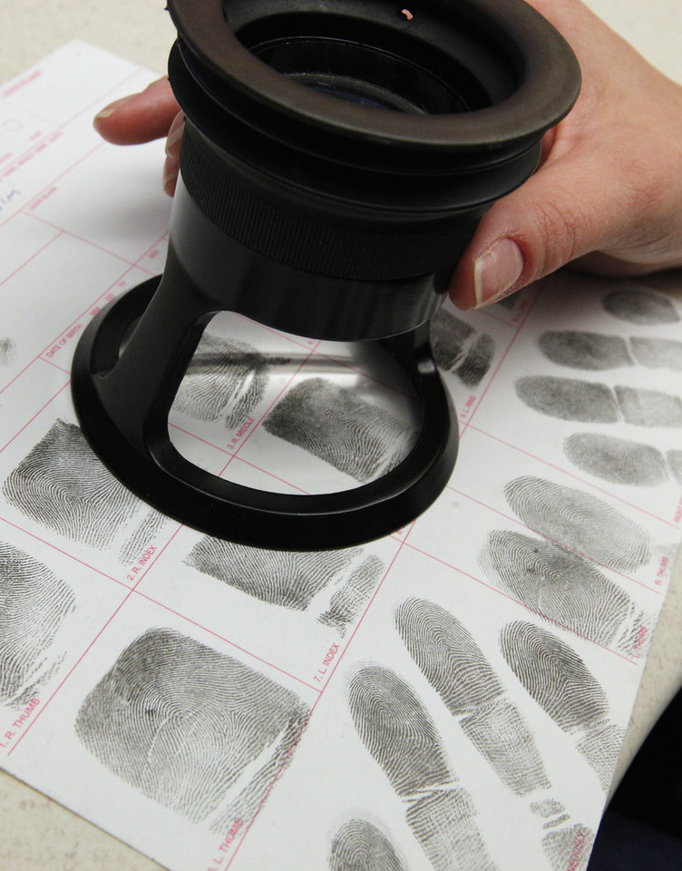 Photo -  A criminalist works in the OSBI Latent Evidence Unit at the Forensic Science Center Friday. Photo by Paul B. Southerland, The Oklahoman   PAUL B. SOUTHERLAND -  PAUL B. SOUTHERLAND