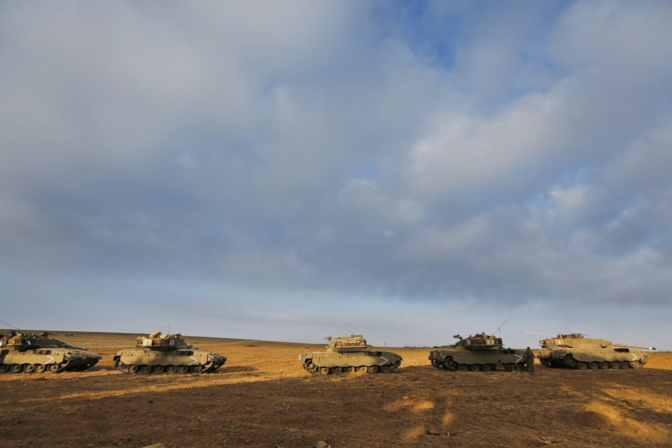 Photo - Israeli army tanks are seen at a staging area on the Israel-Gaza border, Friday, July 11, 2014. Gaza rocket fire struck a gas station and set it ablaze Friday in southern Israel, seriously wounding one person as rocket fire also came from Lebanon for the first time in the four-day-long offensive. Rocket fire by Palestinian militants continued from Gaza toward various locations in southern Israel. (AP Photo/Lefteris Pitarakis)