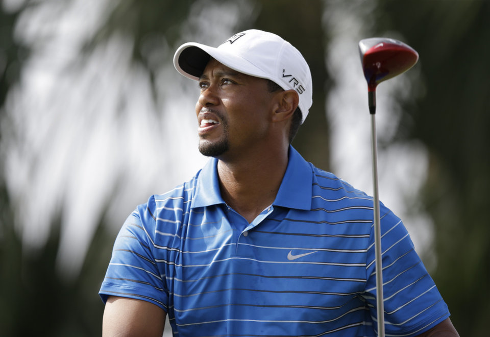 Photo - Golfer Tiger Woods watches his tee shot on the 18th hole during the first round of the Honda Classic golf tournament, Thursday, Feb. 27, 2014 in Palm Beach Gardens, Fla. (AP Photo/Wilfredo Lee)