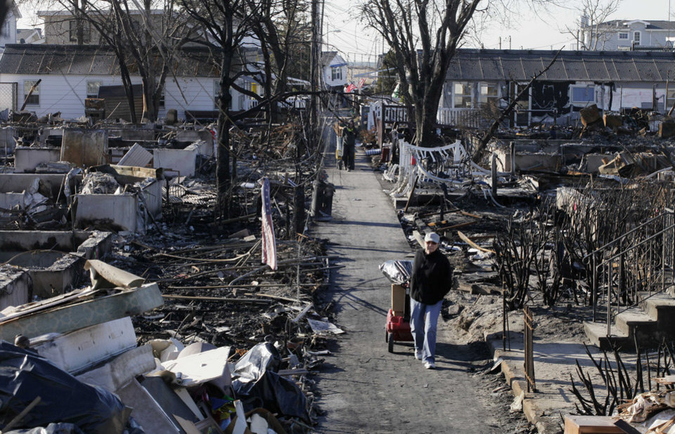 <p>Louise McCarthy carts belongings from her flood-damaged home as she passes charred ruins in the Breezy Point section of the Queens borough of New York, Wednesday, Nov. 14, 2012. A fire destroyed more than 50 homes in the oceanfront community during Superstorm Sandy. (AP Photo/Mark Lennihan)</p>