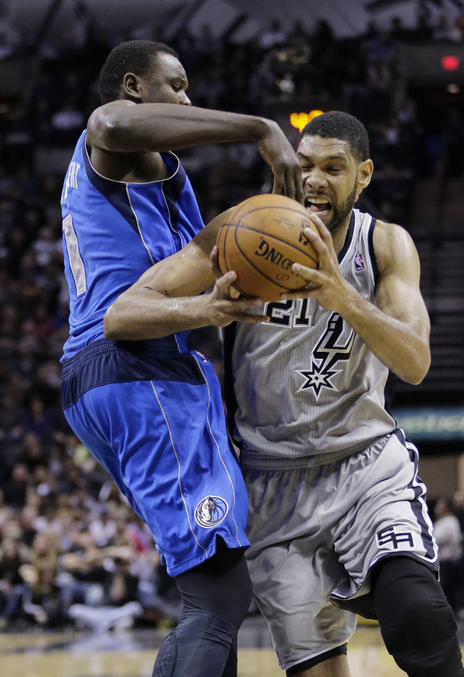 San Antonio Spurs\' Tim Duncan (21) is pressured by Dallas Mavericks\' Samuel Dalembert (1) during the first half of an NBA basketball game, Sunday, March 2, 2014, in San Antonio. (AP Photo/Eric Gay)