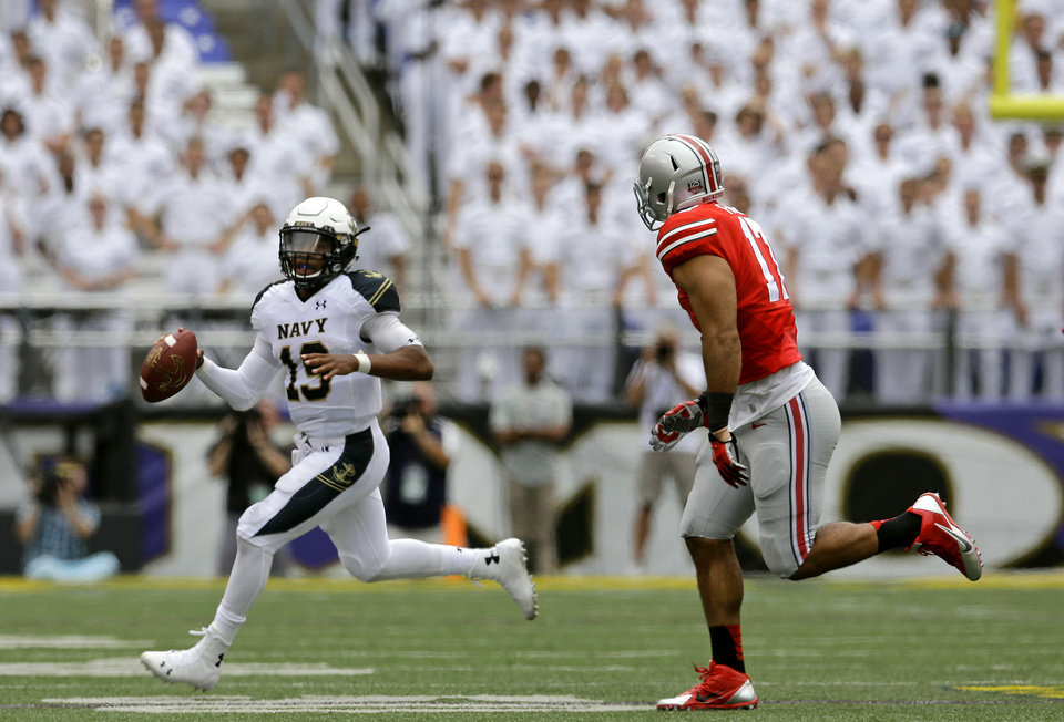 Photo - Navy quarterback Keenan Reynolds, left, looks for a receiver as he tries to evade Ohio State defensive lineman Rashad Frazier during the first half of an NCAA college football game in Baltimore, Saturday, Aug. 30, 2014. (AP Photo/Patrick Semansky)
