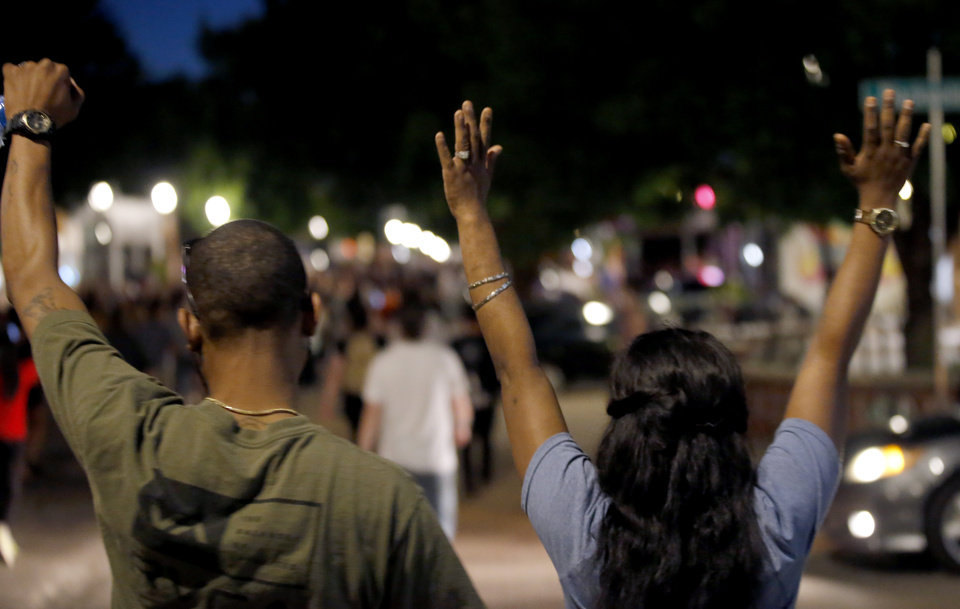 Photo - Protesters hold their hand up in the air as they march during a protest near the intersection of 23rd and Classen in Oklahoma City, Saturday, May 30, 2020. The protest was in response to the death of George Floyd. [Sarah Phipps/The Oklahoman]