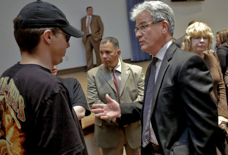 Photo - U.S. Senator Tom Coburn speaks to Joshua Lozier during Coburn's town hall meeting Wednesday at the Metro Tech Springlake campus in Oklahoma City. Photo by Chris Landsberger, The Oklahoman  CHRIS LANDSBERGER