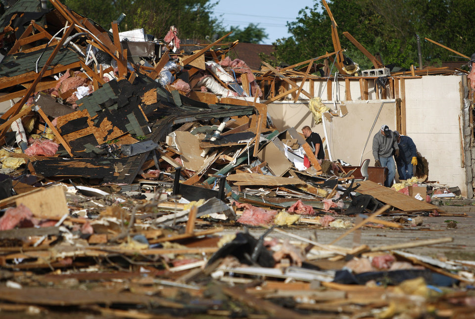 Photo - People pick through debris from a business in Woodward, Okla., Sunday, April 15, 2012. A tornado that killed five people struck Woodward, Okla., shortly after midnight on Sunday, April 15, 2012.  Photo by Bryan Terry, The Oklahoman