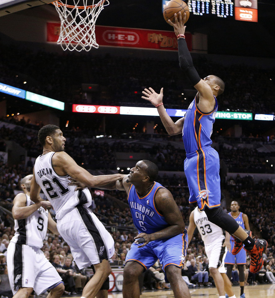 Photo - Oklahoma City's Russell Westbrook (0) shoots as Kendrick Perkins (5) and San Antonio's Tim Duncan (21) watch during Game 1 of the Western Conference Finals in the NBA playoffs between the Oklahoma City Thunder and the San Antonio Spurs at the AT&T Center in San Antonio, Monday, May 19, 2014. Photo by Sarah Phipps, The Oklahoman