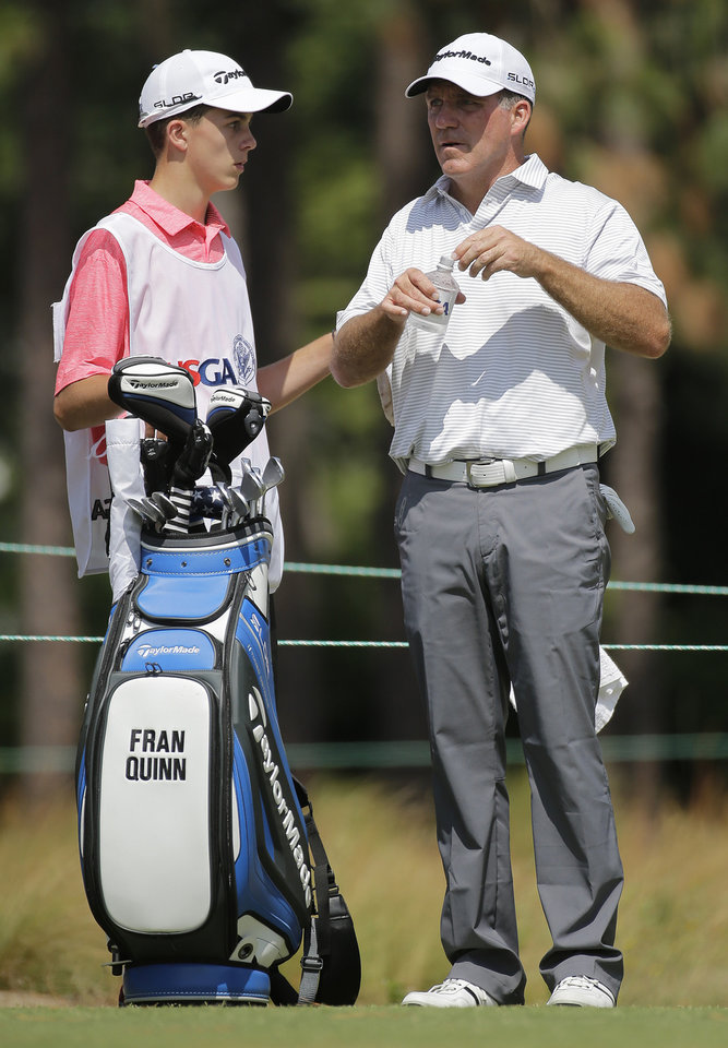 Photo - Fran Quinn, right, talks with his caddie and son Owen Quinn on the 8th hole during the second round of the U.S. Open golf tournament in Pinehurst, N.C., Friday, June 13, 2014. (AP Photo/Eric Gay)