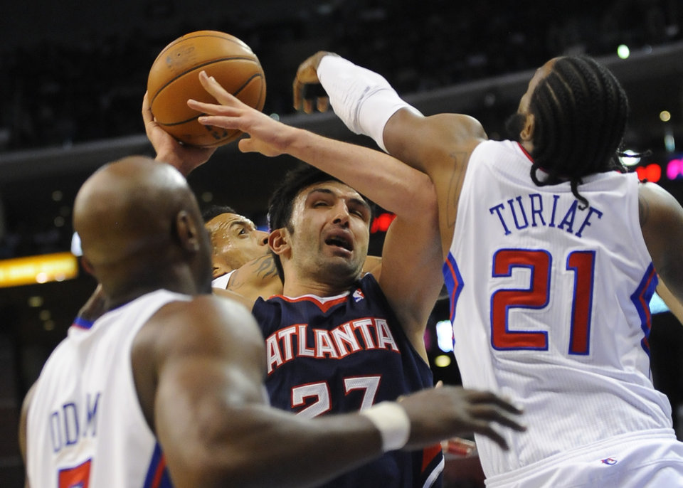 Atlanta Hawks forward Zaza Pachulia (27), of Georgia, battles Los Angeles Clippers center Ronny Turiaf (21), of France, forward Matt Barnes, back center, and Lamar Odom, left, while driving to the basket in the first half of an NBA basketball game, Sunday, Nov. 11, 2012, in Los Angeles. (AP Photo/Gus Ruelas)
