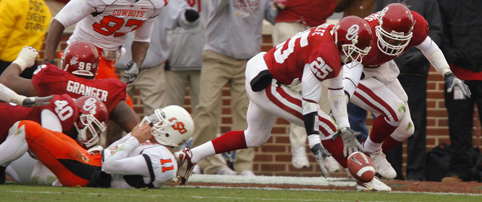 Photo - Oklahoma's D.J. Wolfe (25) and Nic Harris (5) recover a fumble by Oklahoma State's Zac Robinson (11) during the first half of the college football game between the University of Oklahoma Sooners (OU) and the Oklahoma State University Cowboys (OSU) at the Gaylord Family-Memorial Stadium on Saturday, Nov. 24, 2007, in Norman, Okla. 