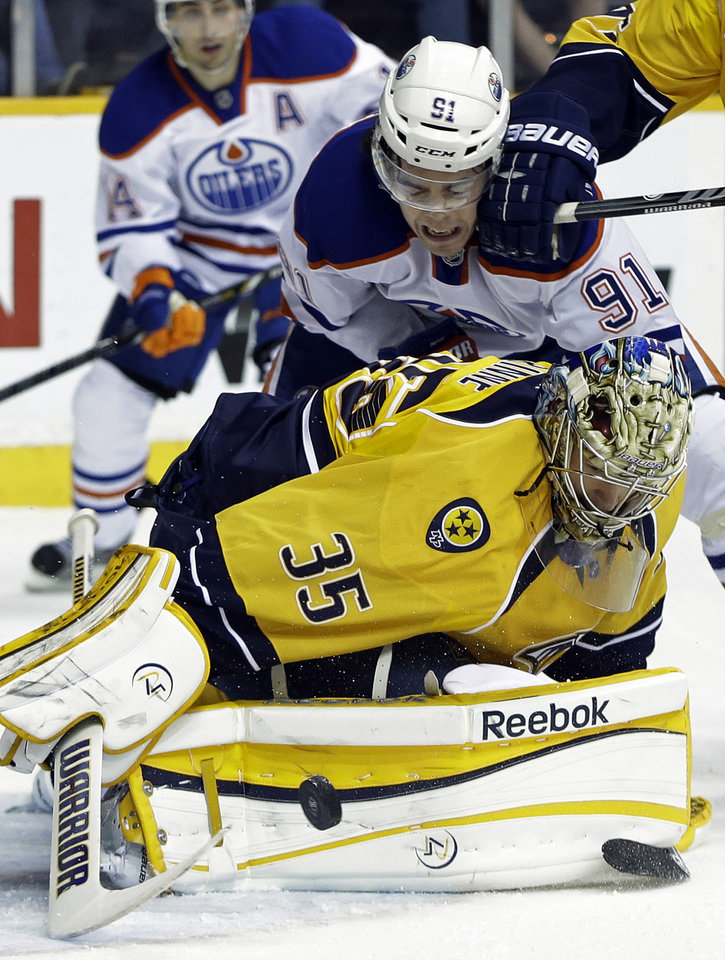 Photo - Nashville Predators goalie Pekka Rinne (35), of Finland, dives on the puck as Edmonton Oilers left wing Magnus Paajarvi (91), of Sweden, gets a glove in the face in the first period of an NHL hockey game on Monday, March 25, 2013, in Nashville, Tenn. (AP Photo/Mark Humphrey)
