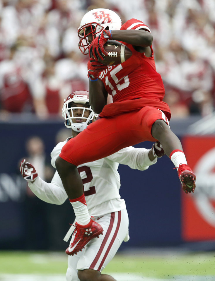Photo - Houston's Linell Bonner (15) catches the ball in front of Oklahoma's Will Johnson (12) during the AdvoCare Texas Kickoff college football game between the University of Oklahoma Sooners (OU) and the Houston Cougars at NRG Stadium in Houston, Saturday, Sept. 3, 2016. Photo by Bryan Terry, The Oklahoman