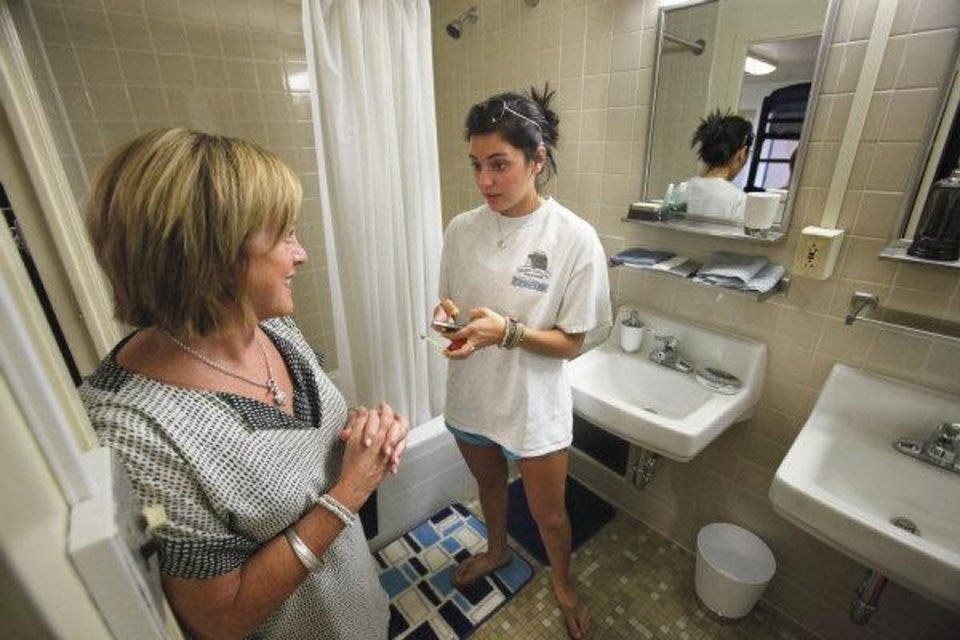 Photo - Incoming University of Oklahoma freshman Rosemary Joseph of Oklahoma City takes measurements in the bathroom of a suite at Walker Tower on the OU campus in Norman.  Photo by Steve Sisney, The Oklahoman ORG XMIT: KOD  STEVE SISNEY - THE OKLAHOMAN