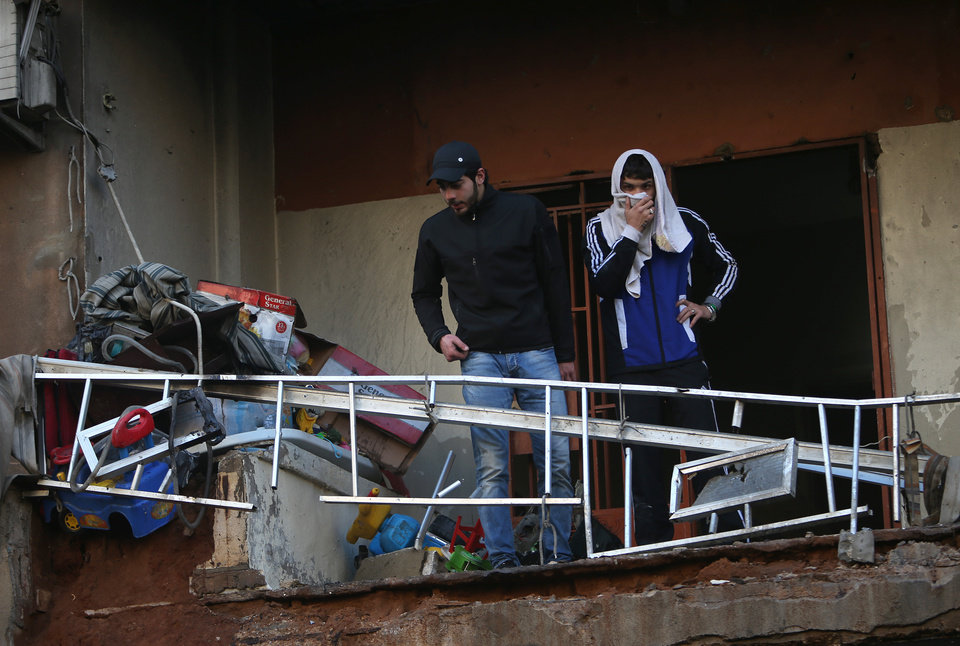Photo - Lebanese residents stand on a damaged balcony at the site of a car bombing in the southern suburb of Beirut, Lebanon, Tuesday, Jan. 21, 2014. A car bomb ripped through a Shiite neighborhood in southern Beirut killing several people and setting plumes of smoke over the area in the latest attack targeting supporters of the militant Hezbollah group in Lebanon. (AP Photo/Hussein Malla)