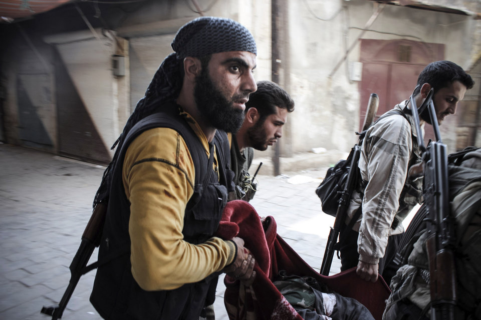Photo -   In this Tuesday, Oct. 30, 2012 photo, Syrian rebels carry a wounded comrade in a blanket away from the frontline in the town of Harem, Syria. (AP Photo/Mustafa Karali)