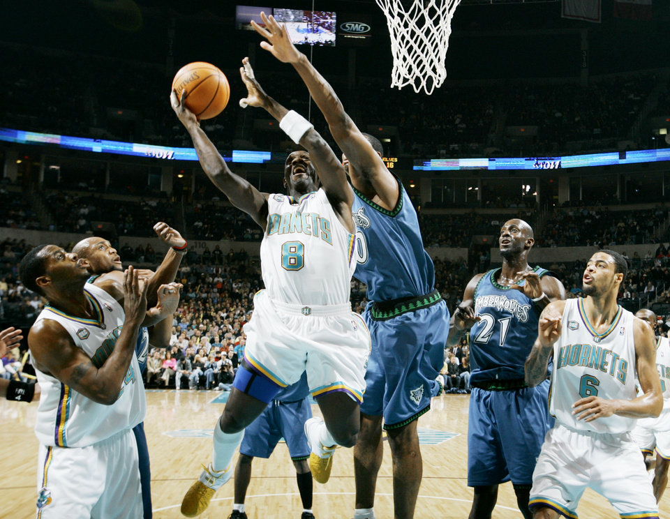 Photo - Hornet Bobby Jackson goes to the basket in front of Timberwolves Trenton Hassell, left, Mark Blount, Kevin Garnett, and teammates Desmond Mason, left, and Tyson Chandler during the New Orleans/Oklahoma City Hornets NBA basketball game against the Minnesota Timberwolves at the Ford Center in Oklahoma City on Friday, Feb., 2, 2007.  By Bryan Terry, The Oklahoman  ORG XMIT: KOD