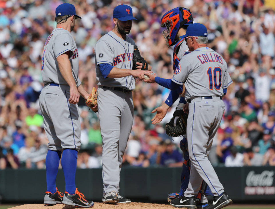 Photo - New York Mets starting pitcher Dillon Gee, second from left, hands the ball to manager Terry Collins (10) while being removed in the seventh inning of the Mets' 5-1 victory over the Colorado Rockies in a baseball game in Denver, Sunday, May 4, 2014. Mets third baseman David Wright, left, and catcher Travis d'Arnaud look on. (AP Photo/David Zalubowski)