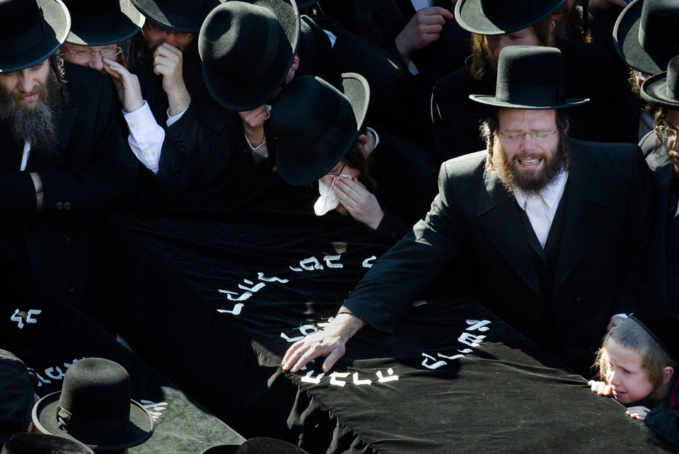Photo - Members of the Satmar Orthodox Jewish community grieve over the coffins at the funeral for two expectant parents who were killed in a car accident, Sunday, March 3, 2013, in the Brooklyn borough of New York. A driver struck the car early Sunday morning, killing both parents while their baby, who was born prematurely, survived and is in critical condition. (AP Photo/John Minchillo)