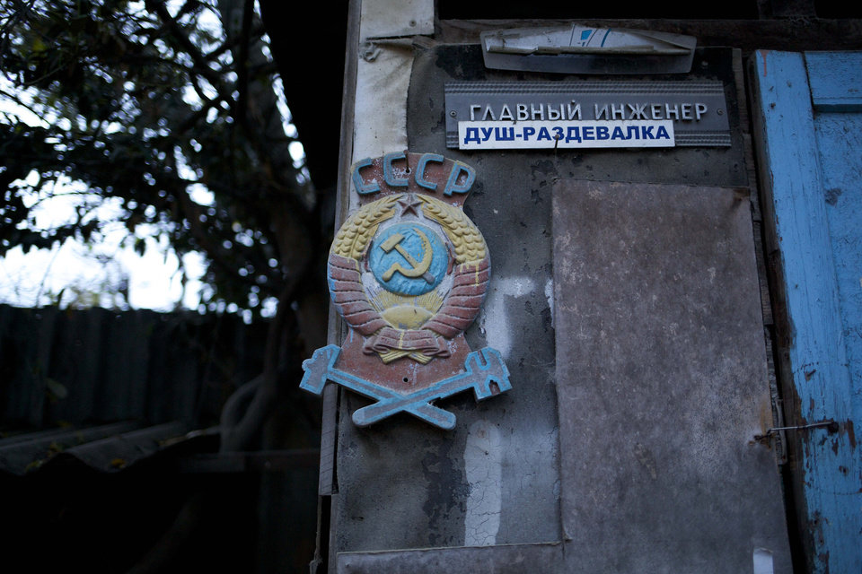Photo - In this photo taken on Wednesday, Nov. 27, 2013, the colored state emblem of the USSR hangs on the door of the outhouse in the yard of the railroad house in the village of Vesyoloye outside Sochi, Russia. Signs read