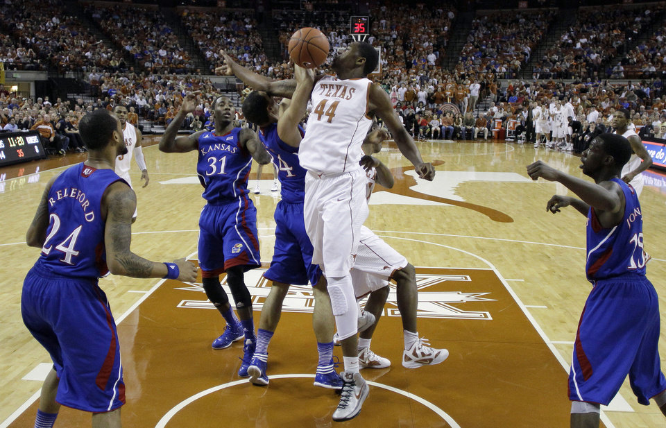 Photo - Texas' Prince Ibeh (44) is blocked by Kansas' Perry Ellis (34) as he tries to score during the first half of an NCAA college basketball game, Saturday, Jan. 19, 2013, in Austin, Texas. (AP Photo/Eric Gay)