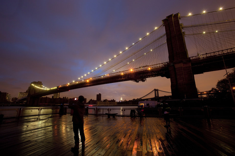 People stop along the Brooklyn waterfront to photograph the Brooklyn Bridge and the Manhattan skyline, Tuesday, Oct. 30, 2012 in New York. Much of lower Manhattan is without electric power following the impact of superstorm Sandy. (AP Photo/Mark Lennihan) ORG XMIT: NYML121