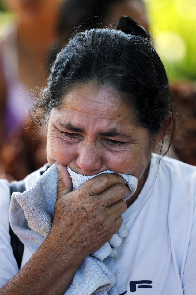 "In this Nov. 15, 2012 photo, Lidia Ortega, 52, cries before a commemorative march in honor of landless farmers who were killed during clashes with police in the Yvy Pyta settlement near Curuguaty, Paraguay. Ortega's husband Delfin Duarte was killed during the ""Massacre of Curuguaty"" on June 15 when negotiations between farmers occupying a rich politician's land ended with a barrage of bullets that killed 11 farmers and 6 police officers. (AP Photo/Jorge Saenz)"