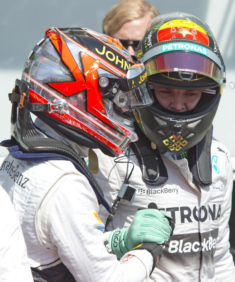 Photo - Mercedes driver Nico Rosberg of Germany, right, shake hands with McLaren driver Kevin Magnussen of Denmark, left, after clocking the fastest time in the qualification at the German Formula One Grand Prix in Hockenheim, Germany, Saturday, July 19, 2014. The German Grand Prix will be held on Sunday, July 20, 2014. (AP Photo/Jens Meyer)