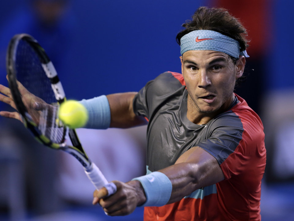 Photo - Rafael Nadal of Spain makes a backhand return to Stanislas Wawrinka of Switzerland during the men's singles final at the Australian Open tennis championship in Melbourne, Australia, Sunday, Jan. 26, 2014.(AP Photo/Rick Rycroft)